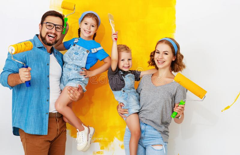 Repair in apartment. Happy family mother, father and children   paints wall. Repair in the apartment. Happy family mother, father  and children   paints the wall stock photography