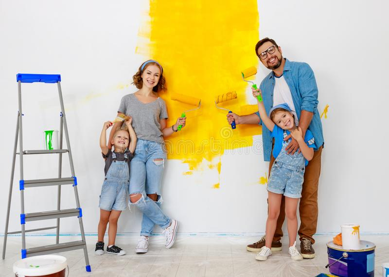 Repair in apartment. Happy family mother, father and children   paints wall. Repair in the apartment. Happy family mother, father  and children   paints the wall stock photo