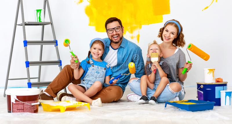 Repair in apartment. Happy family mother, father and children   paints wall. Repair in the apartment. Happy family mother, father  and children   paints the wall royalty free stock image