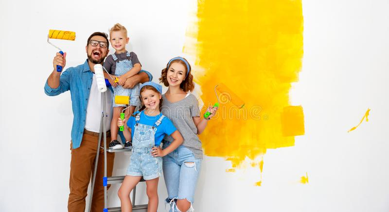 Repair in apartment. Happy family mother, father and children   paints wall stock photos