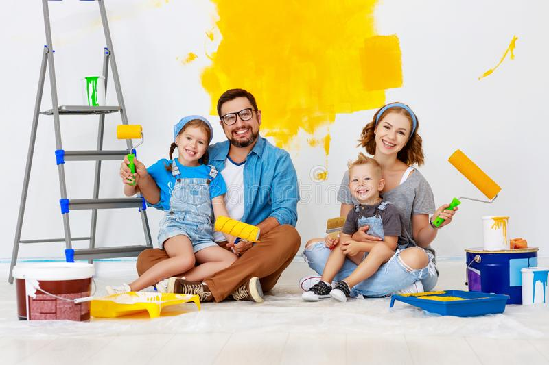 Repair in apartment. Happy family mother, father and children   paints wall stock image