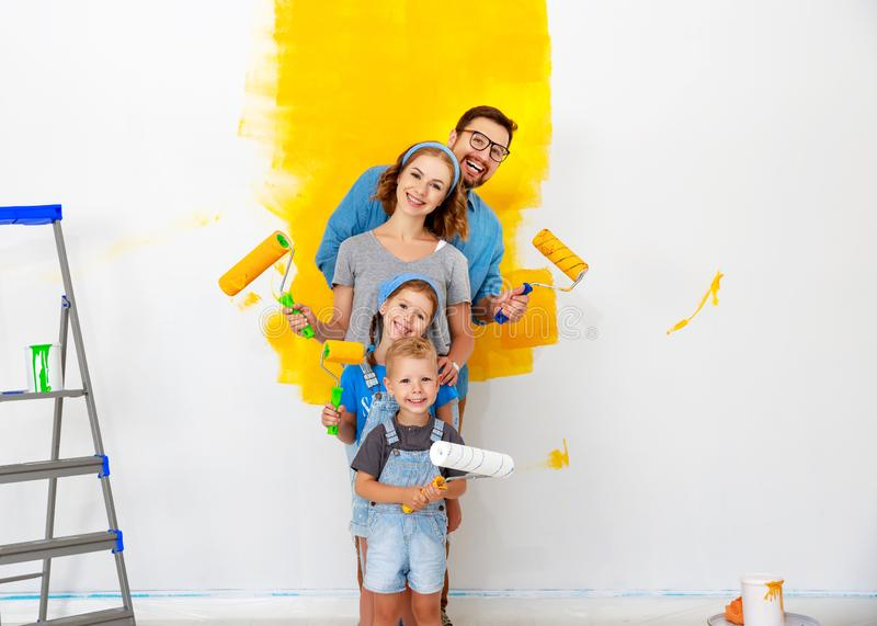 Repair in apartment. Happy family mother, father and children   paints wall royalty free stock photo
