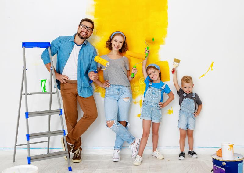 Repair in apartment. Happy family mother, father and children   paints wall. Repair in the apartment. Happy family mother, father  and children   paints the wall royalty free stock photo