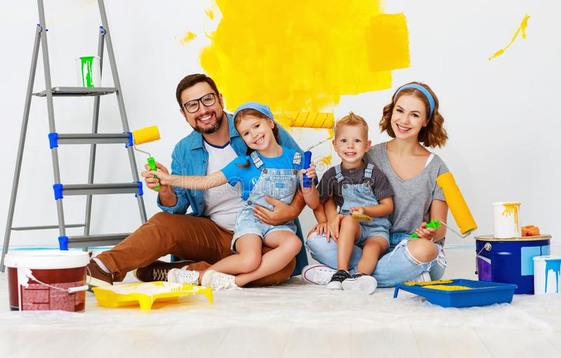 Repair in apartment. Happy family mother, father and children   paints wall. Repair in the apartment. Happy family mother, father  and children   paints the wall royalty free stock images