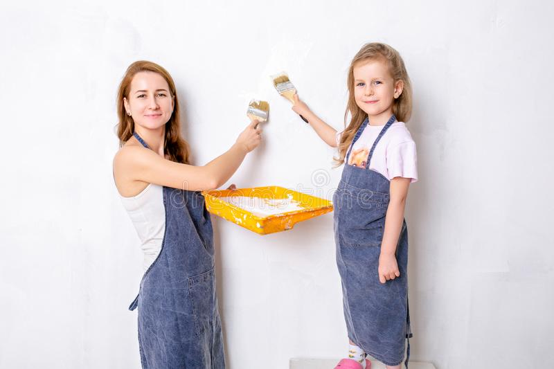 Repair in the apartment. Happy family mother and little daughter in blue aprons paints the wall with white paint royalty free stock photos