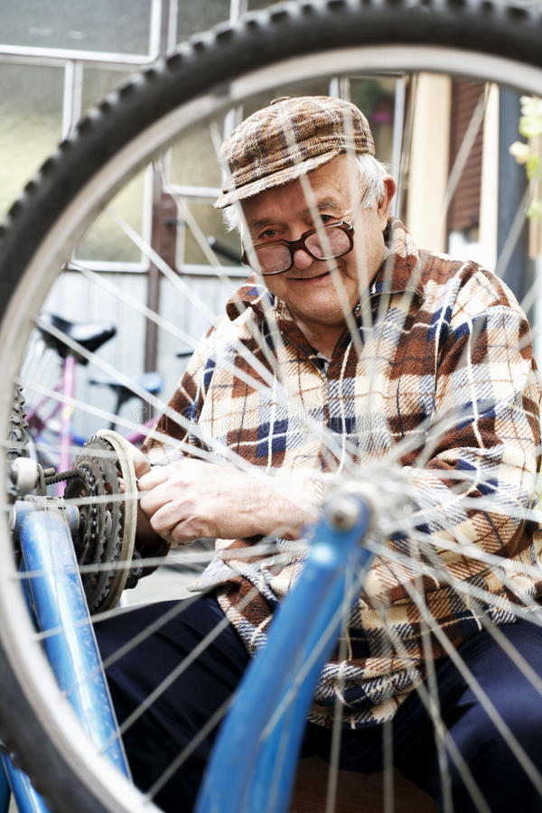 Repair of bicycles hobby is an older man stock images