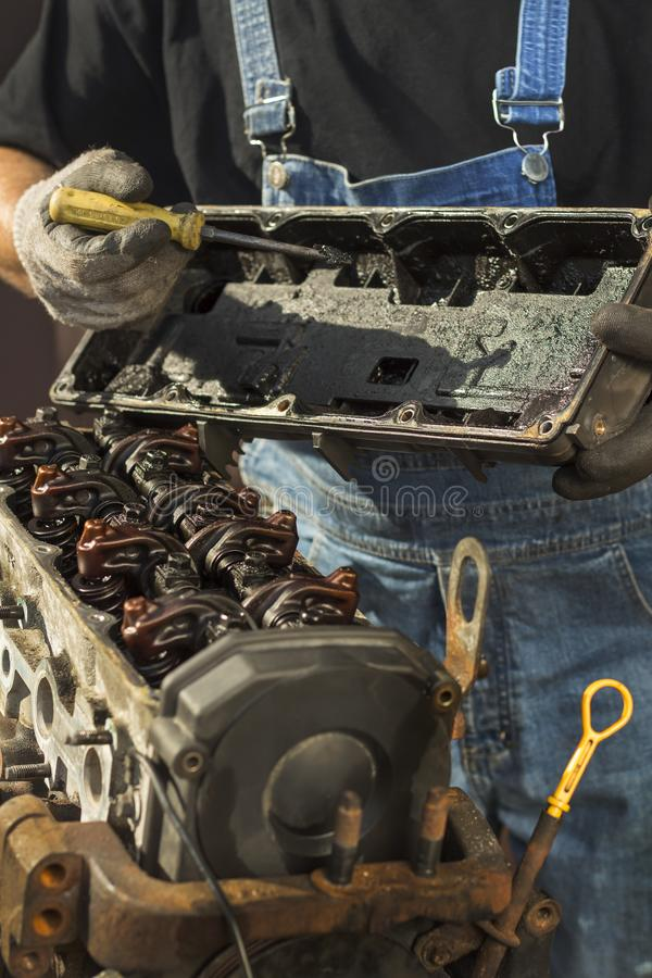 Repair of car engine. The mechanic holds the engine valve cover and shows dirty deposits and deposits on the engine and valve cove. R royalty free stock photography