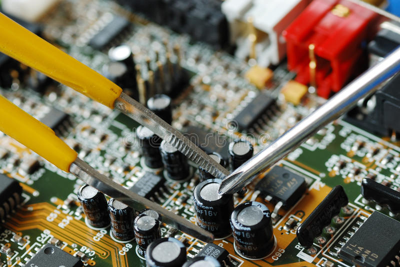 Repair a computer. Repair of the circuit board in a computer stock image