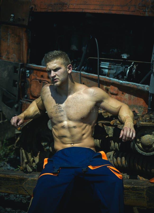 Repair concept. Repair man fix mechanical equipment. Athletic man repair rusty engine and gear. Repair service stock photos