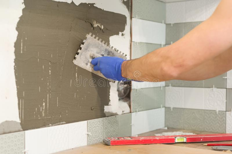 Repair and construction of the kitchen, hands of tiler installing ceramic tiles on the wall, use professional tools, real laying royalty free stock photo
