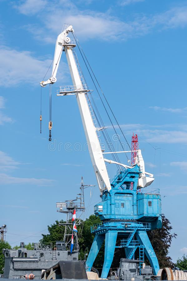 Repair crane in shipyard. Reconstruction old naval ship or unloading cargo ashore. Waiting for ship parts royalty free stock photography