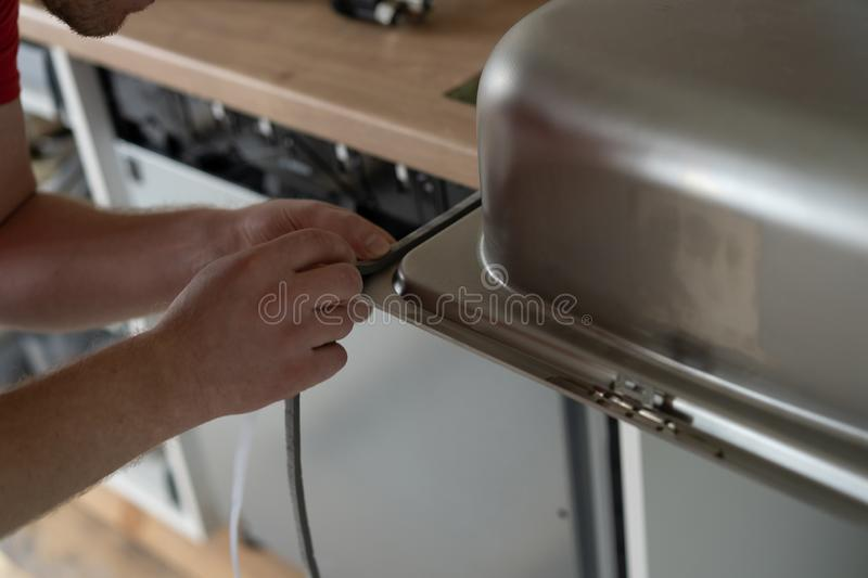 Repair and decoration. master sets the sink in the kitchen.  royalty free stock image