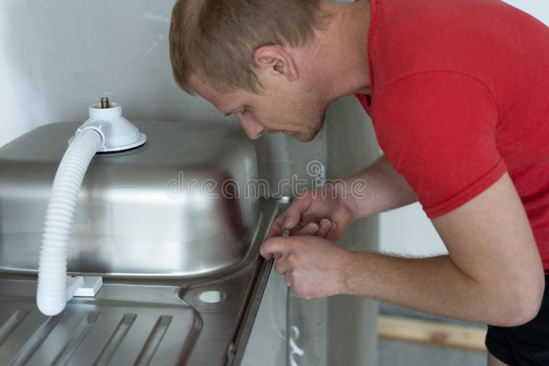 Repair and decoration. master sets the sink in the kitchen.  royalty free stock photos