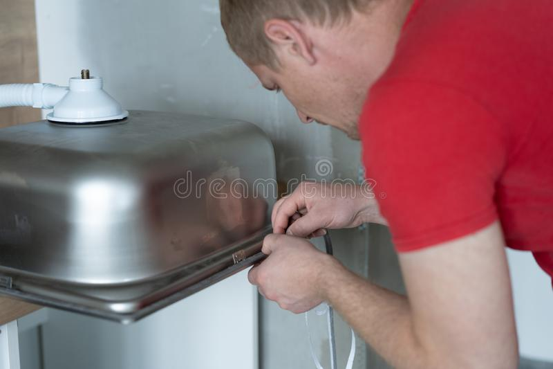 Repair and decoration. master sets the sink in the kitchen.  royalty free stock images