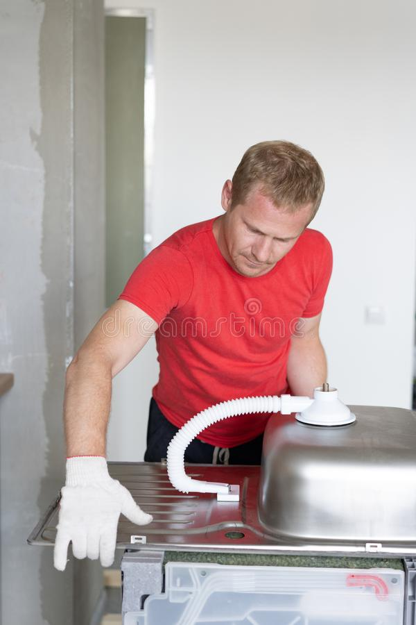 Repair and decoration. master sets the sink in the kitchen.  stock photos