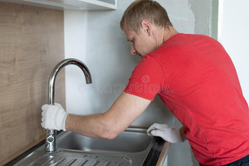 Repair and decoration. plumber repairing water pipes in the kitchen under the sink.  stock images