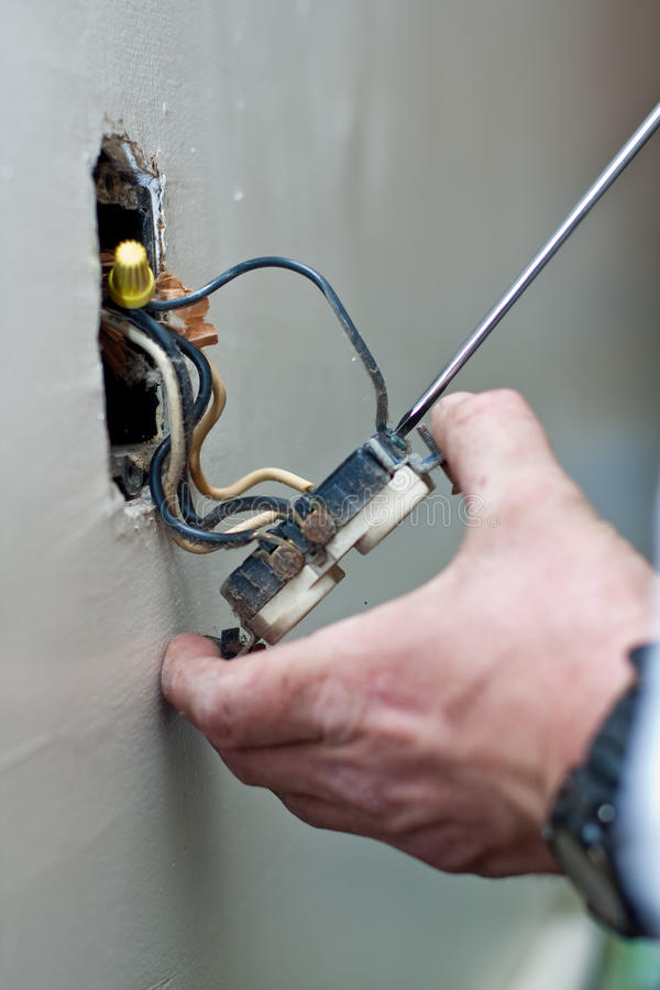 Repair of electric wall outlet. An electrician is using a screwdriver to repair an old electric wall outlet. Wires are visible royalty free stock photos