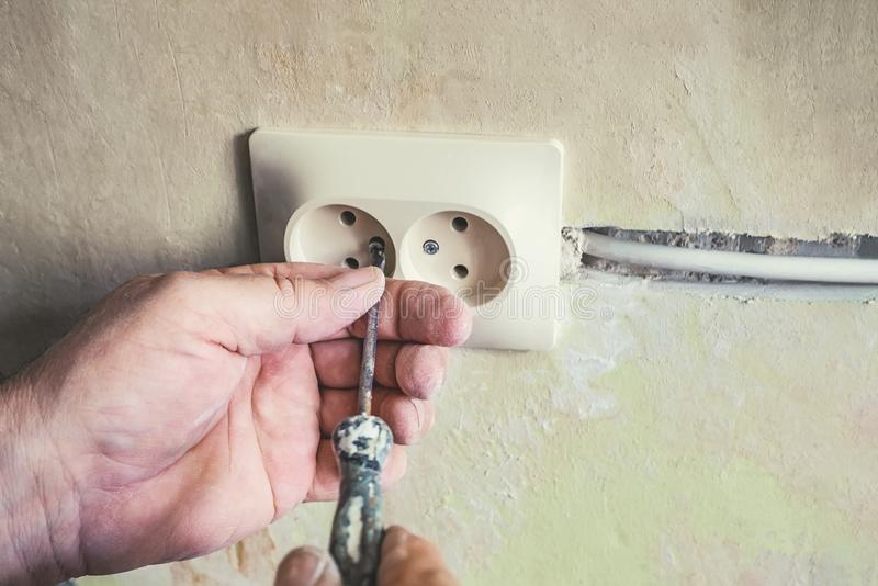 Repair of electrical outlets in the wall of the house.Old broken light switch with power connection in old broken factory. royalty free stock images