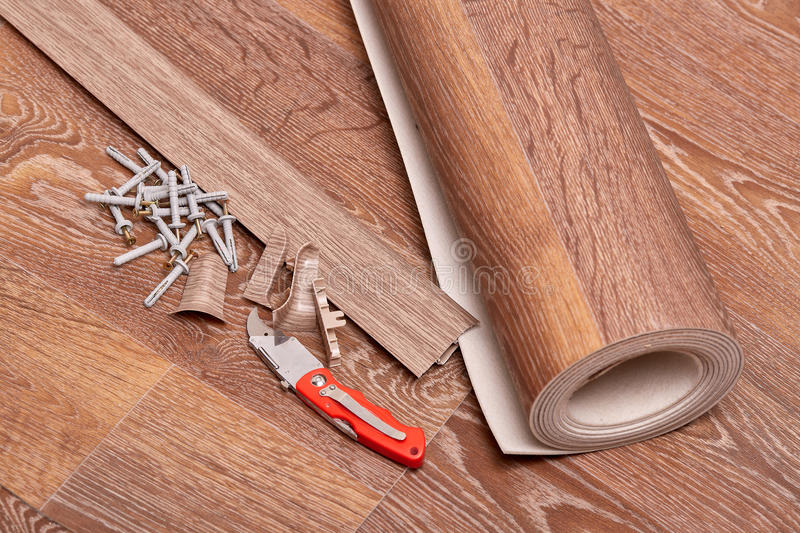 Repair of a floor covering. A roll of linoleum, baseboards, fasteners are laying on the new floor covering. Home repair royalty free stock images