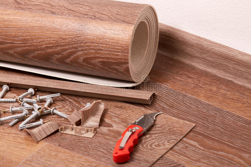 Repair of a floor covering. A roll of linoleum, baseboards, fasteners are laying on the new floor covering. Home repair royalty free stock photos