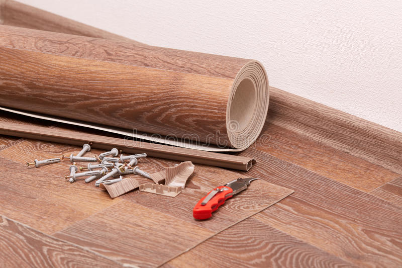 Repair of a floor covering. A roll of linoleum, baseboards, fasteners are laying on the new floor covering. Home repair stock photos