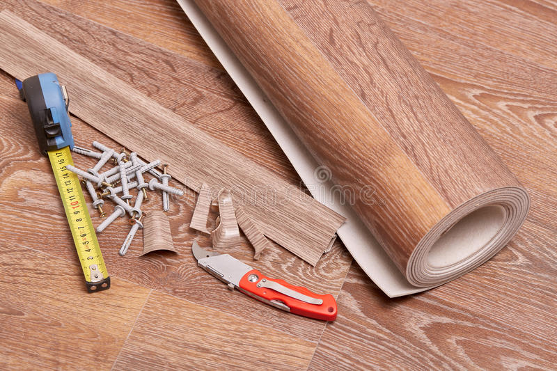 Repair of a floor covering. A roll of linoleum, baseboards, fasteners are laying on the new floor covering. Home repair royalty free stock photography