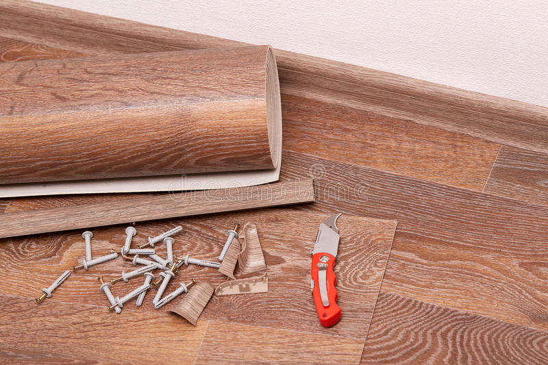 Repair of a floor covering. A roll of linoleum, baseboards, fasteners are laying on the new floor covering. Home repair royalty free stock photo