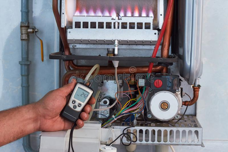 Repair of a gas boiler, setting up and servicing by a service department. Adjustment of gas pressure by manometer stock images
