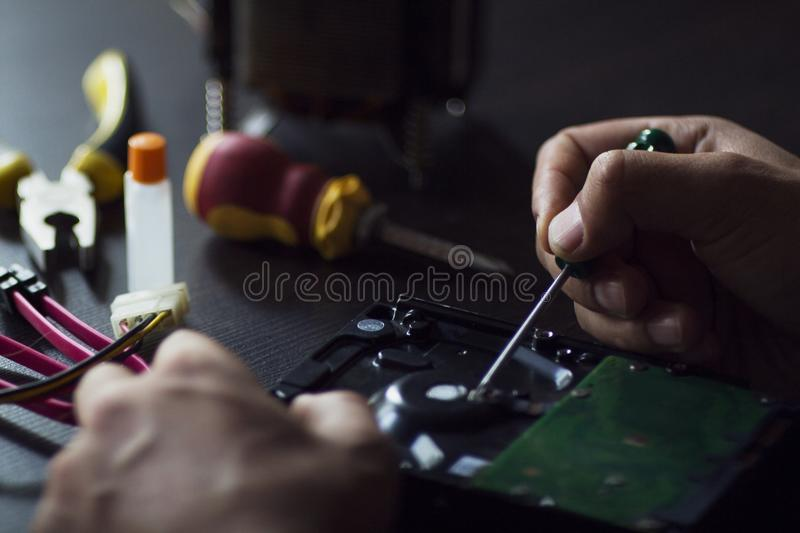 Repair hard disk. Hand repair the hard drive on the service royalty free stock image