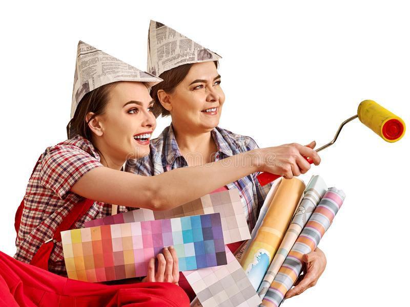 Repair home women holding Bank with paint for wallpaper. Repair home women holding color guide for wallpaper. Elderly mother and young daughter renovation royalty free stock image