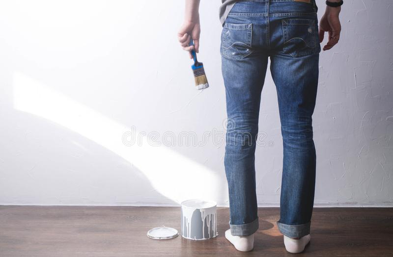 Repair of the house: the man is going to paint the wall with a brush in white. The paint drips from the brush. A view of the legs and hand stock images