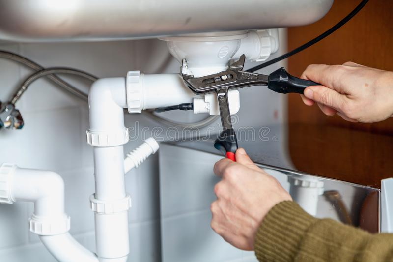 Repair of kitchen overflow pipe wrench closeup stock photos