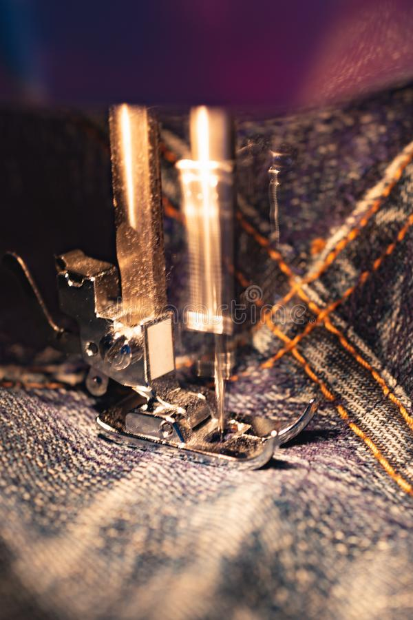 Repair jeans on the sewing machine. View of the fabric, needle and thread. Real motion blur. Lit by the built-in incandescent lamp. Jeans are a type of royalty free stock images