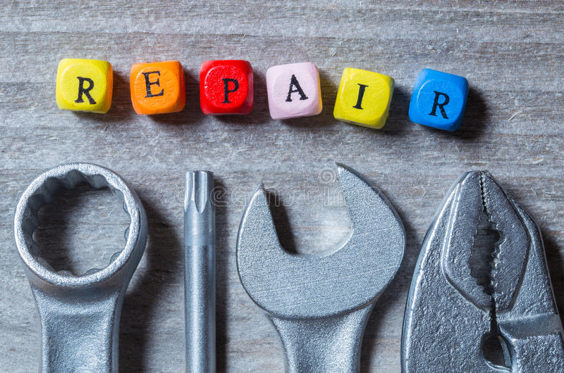 Repair letter cubes and tool on gray wood visualization royalty free stock photos