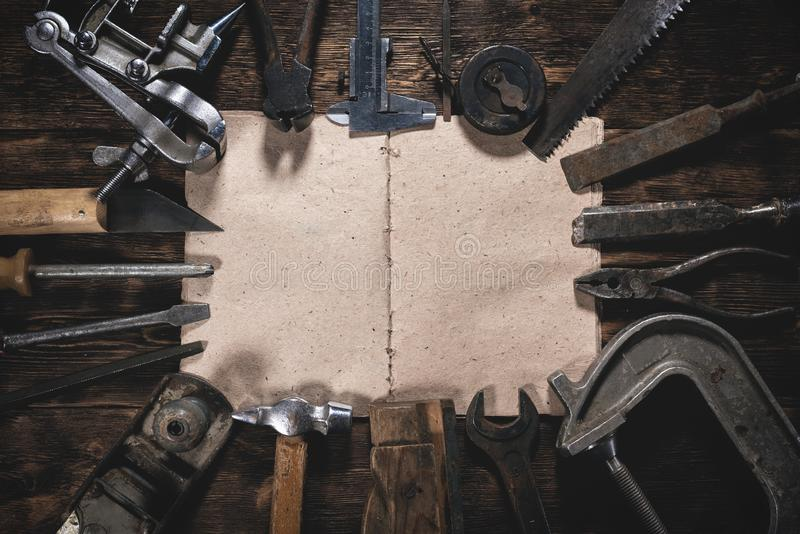 Repair list. To do list mock up. Construction handbook with blank pages and old construction tools on a wooden workbench flat lay background. Carpentry stock image
