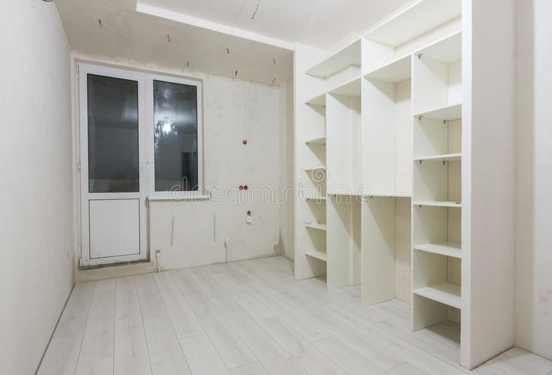 Repair in living room of new buildings, built-in wardrobe and on the floor laminated panels. Repair in the living room of new buildings, built-in wardrobe and on stock images