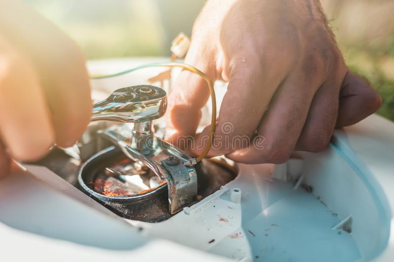Repair and maintenance of the water heater. The man spins a detail of the wrench. Hands close up. Light stock photography