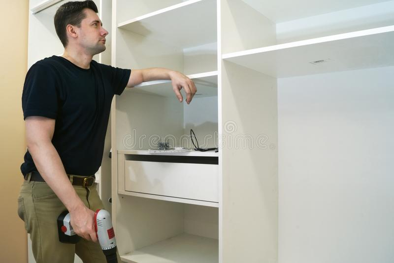 Repair man looking at cupboard or wardrobe. royalty free stock photos