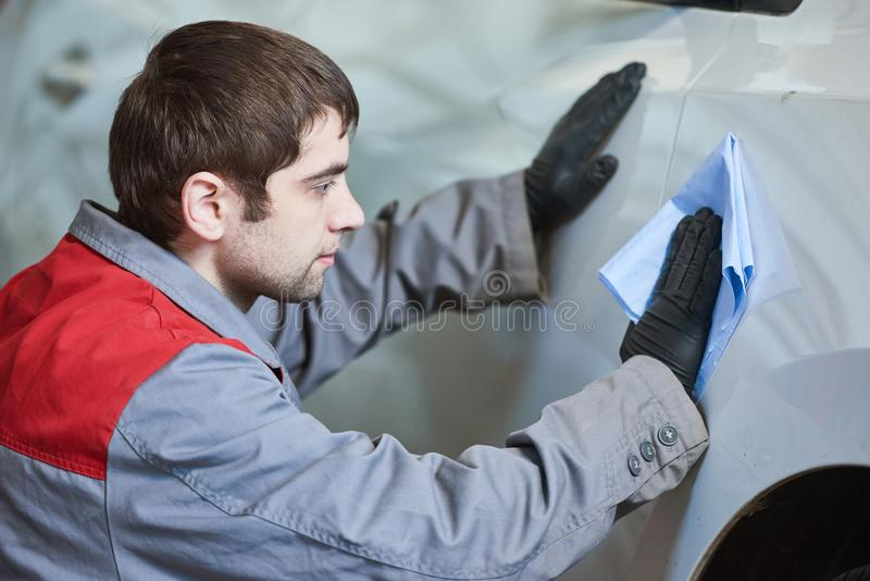 Repair man worker cleaning automobile car body in garage royalty free stock photos
