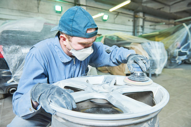 Repair mechanic worker with light alloy car wheel disk rim. Auto repair mechanic worker with light alloy car wheel disk rim during refurbish at garage service stock photo