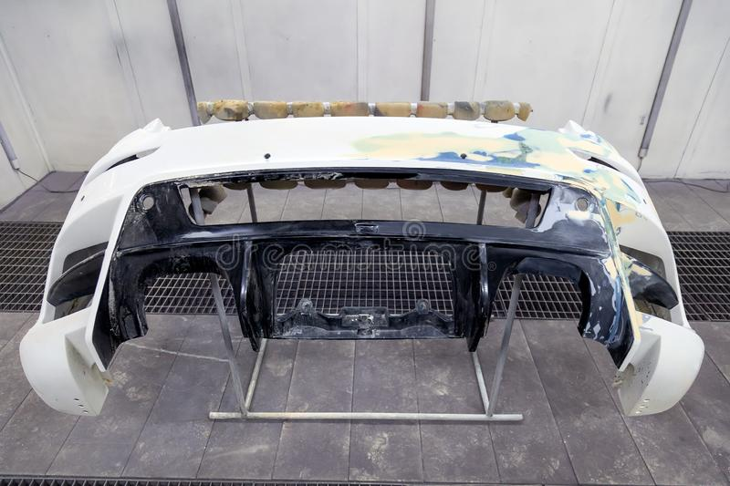 Repair of the rear bumper of a white car after an accident with the help of multi-colored putty in a workshop for painting stock photography