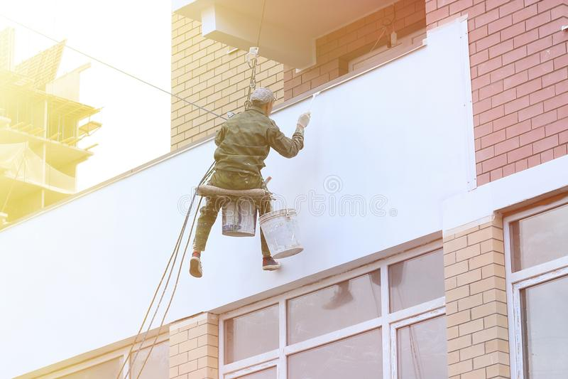 Repair and restoration of a facade of a building. painting color on building wall. facade builder worker with brush, working on hi. Gh building. safety royalty free stock images