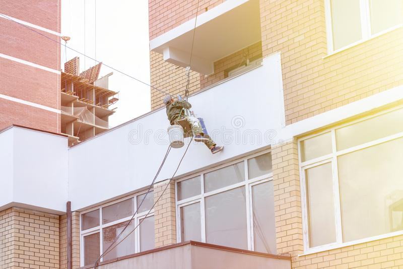 Repair and restoration of a facade of a building. painting color on building wall. facade builder worker with brush, working on hi. Gh building. safety stock photo