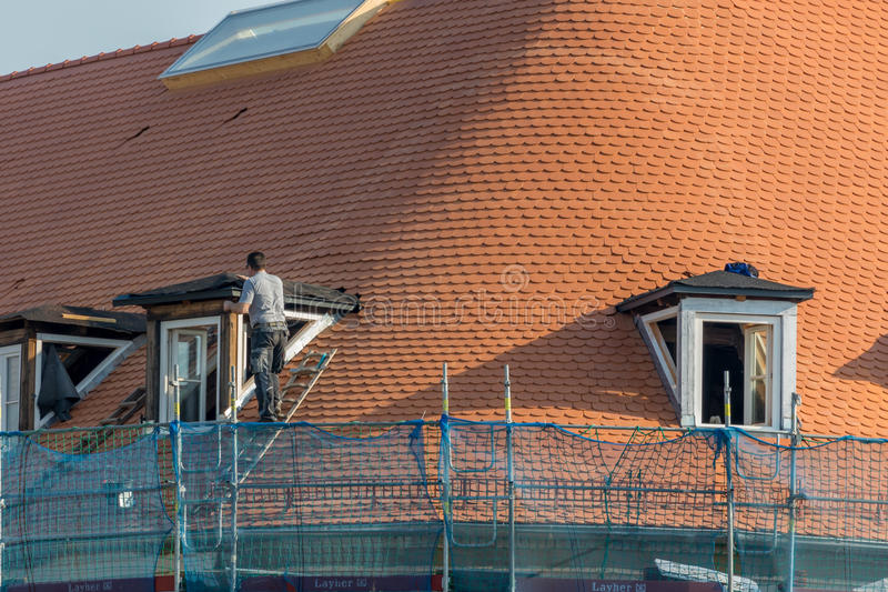 Repair a roof - Safety first. Repair the roof of an old historical building royalty free stock photo