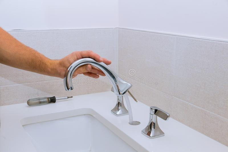 Repair service, assemble new faucet lies on the ceramic sink royalty free stock photo