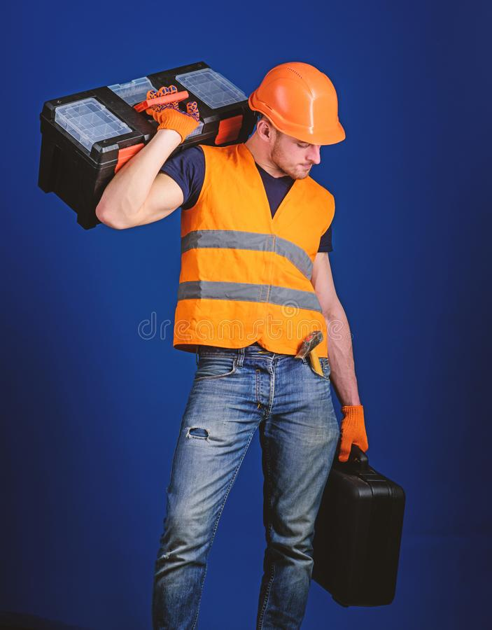 Repair service concept. Man in helmet, hard hat holds toolbox and suitcase with tools, blue background. Worker, repairer stock photos
