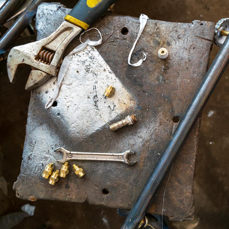 Repair tools placed on grunge rusted metal table. From above wrenches and screws placed on shabby metal table in workshop stock photos