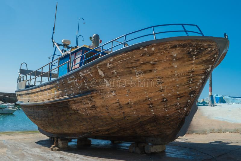 Repair of wooden boats in dry-dock. Boats are raised and waiting royalty free stock photo