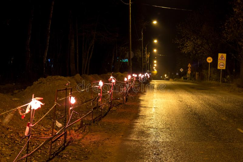 Allocation of the work site in the evening by lamps. Repair work along the road. Allocation of the work site in the evening by lamps royalty free stock photography