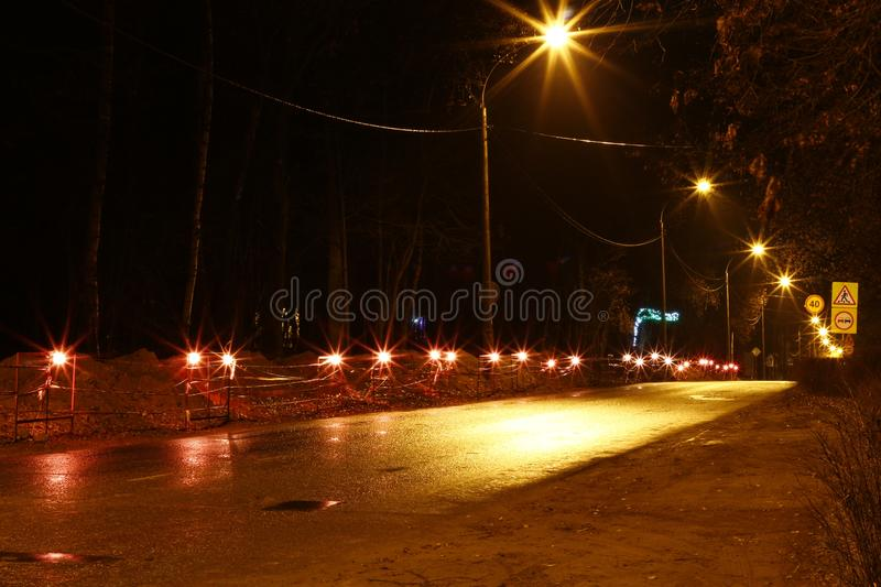 Allocation of the work site in the evening by lamps. Repair work along the road. Allocation of the work site in the evening by lamps royalty free stock photo